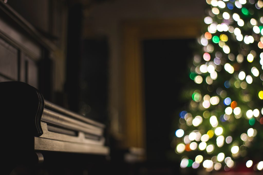 Piano with blurred Christmas tree